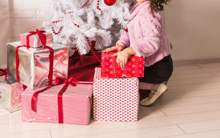 sincere girl: happy little child with gifts and Christmas tree. Stock Photo