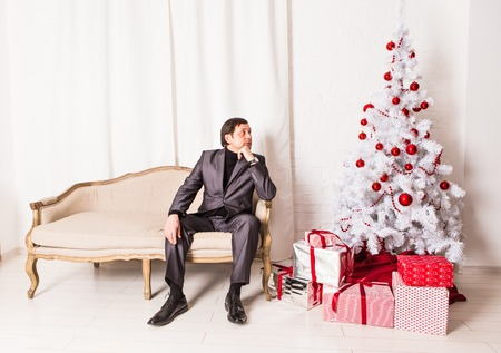 fireplace living room: Men and Christmas tree with presents near the fireplace at home in the living room Stock Photo