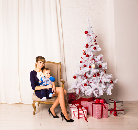 Smiling mother playing with  baby near Christmas tree.
