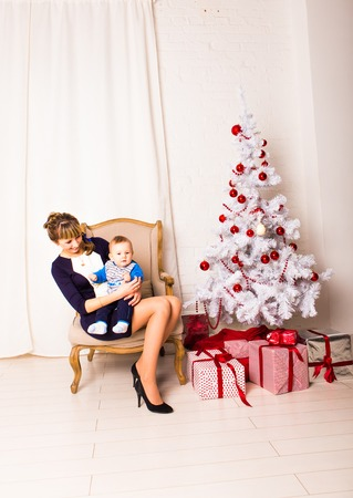 santa s helper: Smiling mother playing with  baby near Christmas tree.