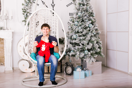 baby near christmas tree: Happy young father and baby near Christmas tree. Stock Photo