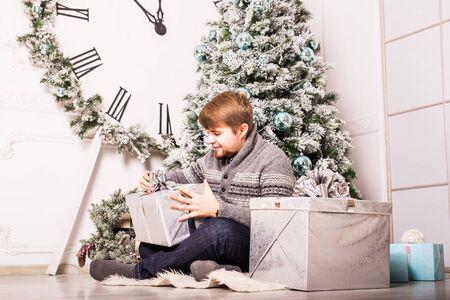 dar un regalo: hombre joven y feliz con los regalos. tiempo de Navidad Foto de archivo