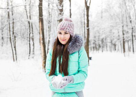 poses de modelos: Joven y bella muchacha sonriente la celebración de nieve en manos. Foto de archivo