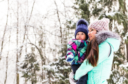 baby playing: happy family mother and child baby daughter on a winter walk in the woods. Stock Photo