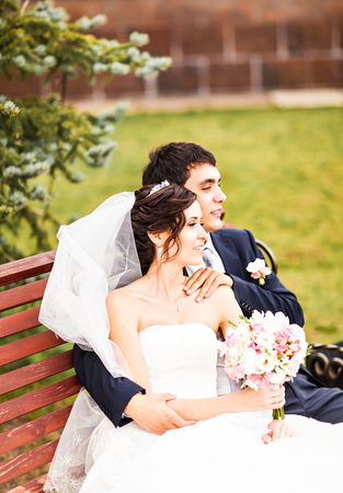 spousal: The bride and groom sitting on a bench in the Park.