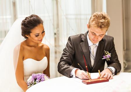 Novia firma contrato de licencia de matrimonio o boda. Foto de archivo