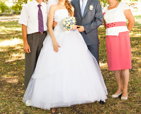 newly married couple: Portrait of a newly married couple embracing with parents standing in the background. Stock Photo