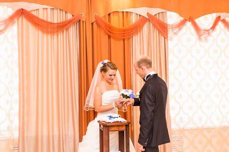 Bruid die een ring op de vinger van de bruidegom tijdens de huwelijksceremonie.