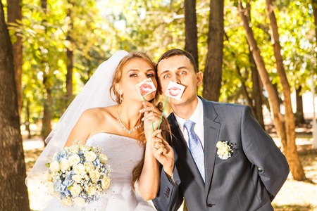 Wedding couple posing with stick lips, mask. Wedding accessories Standard-Bild