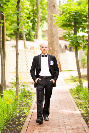 on looker: Portrait of the groom in the park on their wedding day.Rich groom on their wedding day