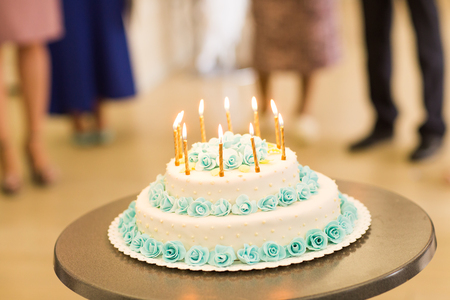 white candle: Birthday cake with candles. Cake with blue cream roses Stock Photo