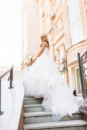makeups: Beautiful bride in magnificent dress stands alone on stairs. Stock Photo