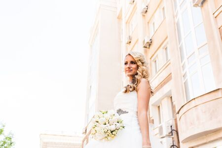 upsweep: Beautiful bride in magnificent dress stands alone on stairs. Stock Photo