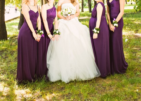 bridesmaids: The bride and bridesmaids are showing beautiful flowers on their hands. Stock Photo
