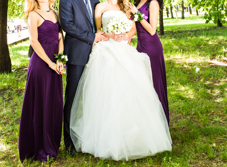 bridesmaids: Bride with groom and bridesmaids near trees.