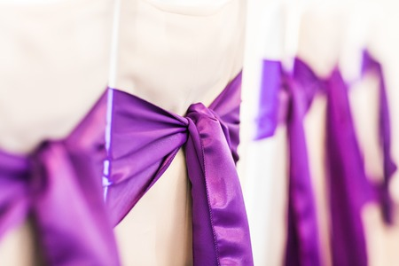 wedding chairs: White wedding chairs decorated with purple bows. Stock Photo