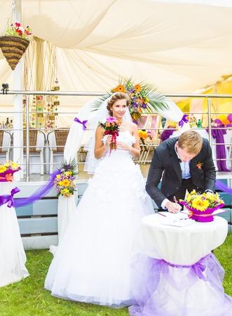alimony: Wedding ceremony. Wedding couple leaving their signatures Stock Photo