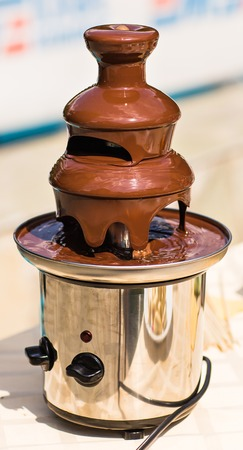 tempt: Chocolate fountain placed on a table in wedding day.