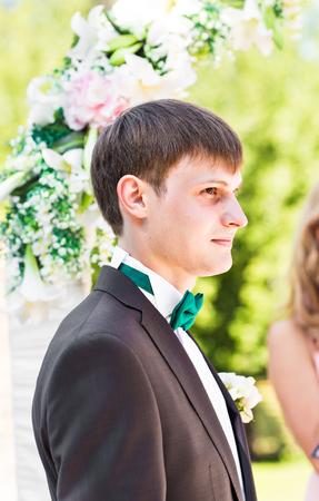 uomini belli: sposo bello in vestito sulla natura. Ritratto maschile nel parco. Bello modello ragazzo in abiti da sposa colorati. L'uomo sta proponendo. Bel ragazzo all'aperto