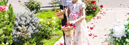 goodliness: Girl and boy holding a basket with wedding flowers and rose petals Stock Photo
