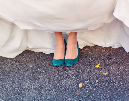 Bride  show off her turquoise shoes at wedding.