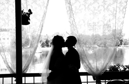 trash the dress: Happy newlyweds kissing indoor. Brunette bride  and  groom stand near window silhouettes of happy. Stock Photo
