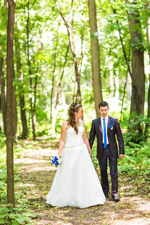 newly married couple: Newly married couple walk on park paths holding hands. Stock Photo