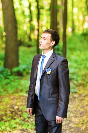 on looker: Portrait of the groom in the park on their wedding day. Stock Photo