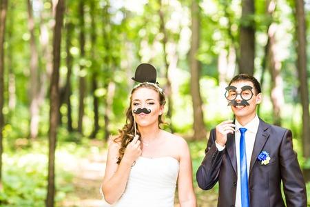Wedding couple posing with stick lips, mask. April Fools' Day. Standard-Bild