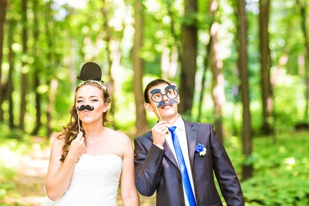 Wedding couple posing with stick lips, mask. April Fools' Day. Stock Photo