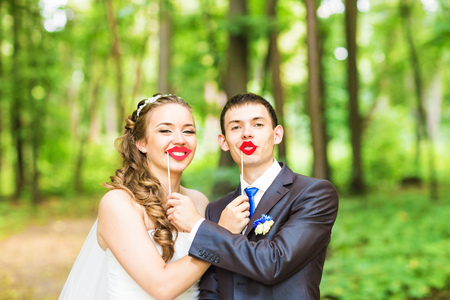 Wedding couple posing with stick lips, mask. April Fools Day.