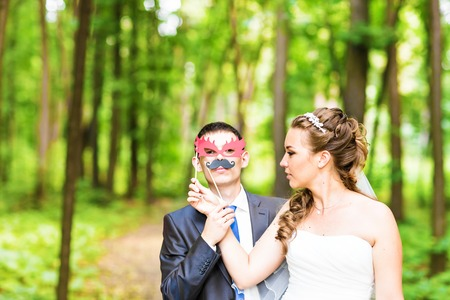 Wedding couple posing with stick lips, mask. April Fools' Day. 写真素材