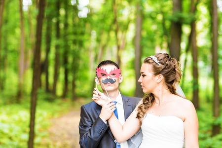 Brautpaar posiert mit Stick Lippen, Maske. Erster April.