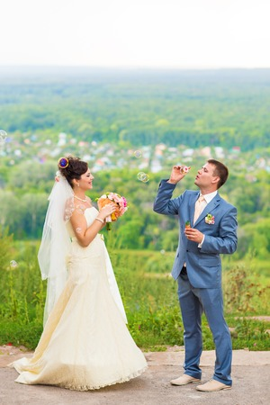 blubber: beautiful young wedding couple blowing bubbles outdoors