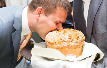 traditional custom: traditional wedding custom to bite a large piece of bread. Stock Photo