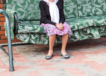 swing seat: Grandmother  sitting alone on outdoor swing seat Stock Photo