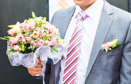 groom holding wedding bouquet. Beautiful bridal bouquet