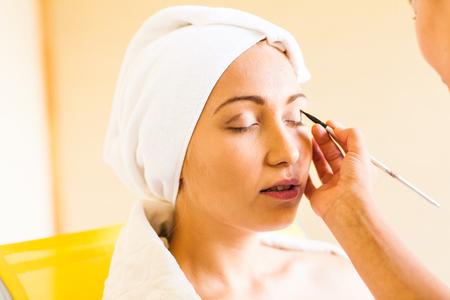 estilista: Stylist applying make-up to young beautiful woman. Foto de archivo
