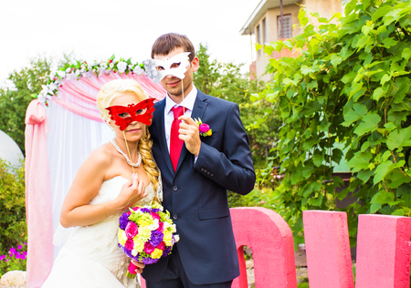 scruple: Bride and groom with funny carnival masks.