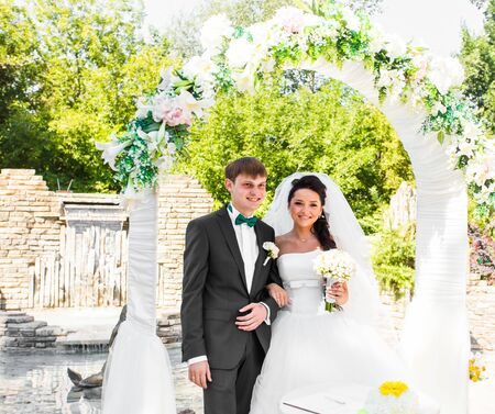 bridegrooms: Bride and Groom Under Archway. Wedding day Stock Photo