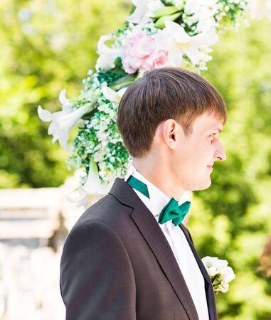 fingers put together: elegant stylish groom having wedding ceremony on the background of arch. Stock Photo