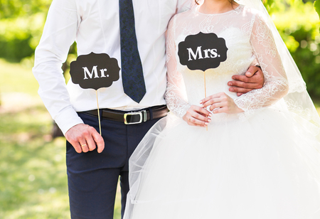 mr and mrs: Funny bride and groom with Mr and Mrs signs. Happy wedding day. Stock Photo