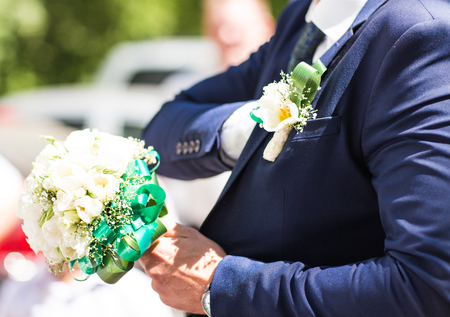 buttonhole: Beautiful wedding bouquet in hands of the groom. Gift to the bride.Blue classic designer suit with  buttonhole Stock Photo