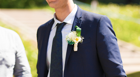 buttonhole: the groom in a blue suit with a buttonhole of flowers and greenery.