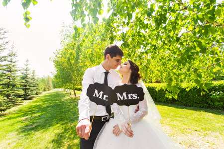 mr: Funny bride and groom with Mr and Mrs signs. Happy wedding day. Stock Photo