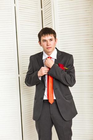cufflink: groom straightening his bowtie. Businessman straightens his tie Stock Photo