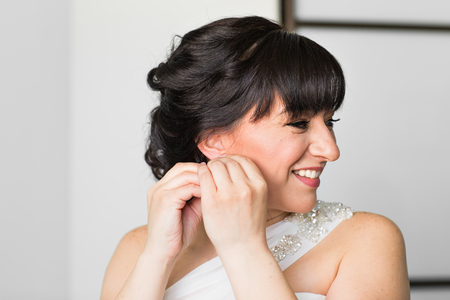 put: beautiful woman put earring and smiling portrait. Stock Photo