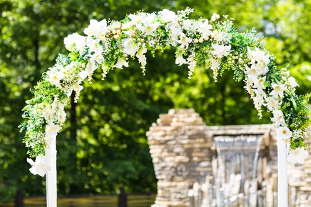 Beautiful white wedding arch decorated with white flowers outdoors.
