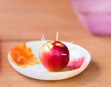 stab: toothpicks stab into red apple.  Apple on a plate