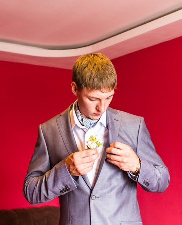 buttonhole: Groom in a suit holding buttonhole. Wedding Stock Photo